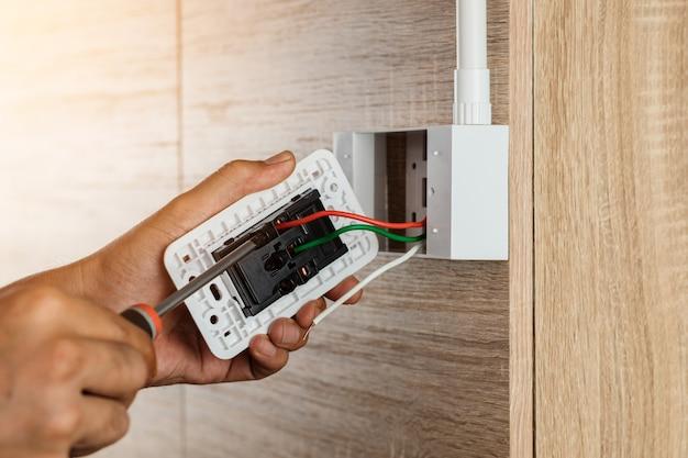 De hand van een elektricien gebruikt een schroevendraaier om de draden aan het stopcontact te bevestigen.