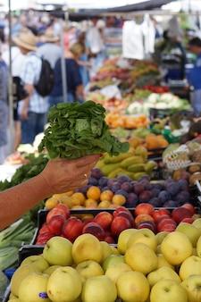 De hand van een gebruinde vrouw strekt een salade uit over de toonbank in de groentemarkt