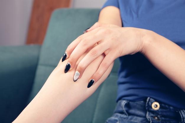 De hand van een jonge vrouw jeukt terwijl ze op de bank zit