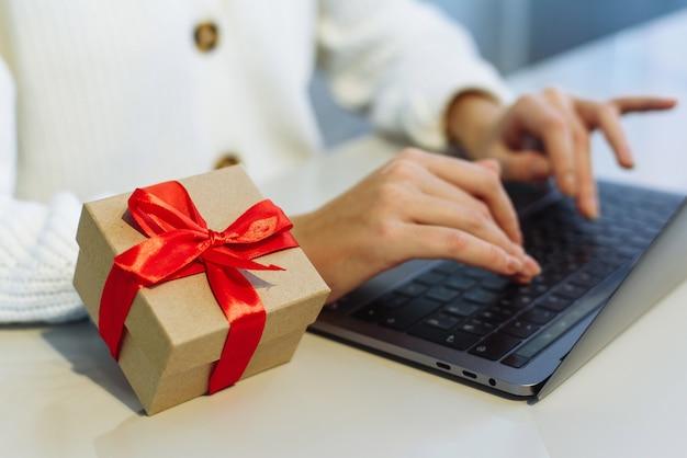 De hand van een jonge vrouw ligt op het toetsenbord van de laptop naast een kerstcadeau met een rood lint.