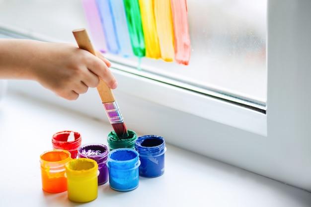 De hand van een kind doopt een penseel in verf.