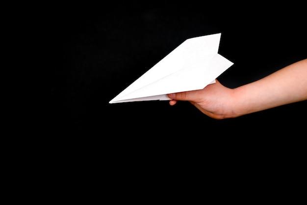 De hand van een kind houdt een papieren vliegtuigje op een zwarte.