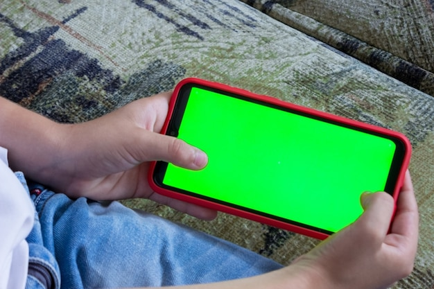 De hand van een kind houdt een smartphone in een horizontale positie met een groen scherm, chromakey, mock-up.