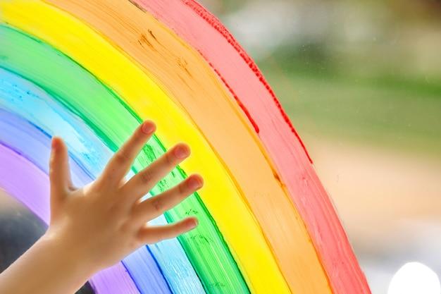 De hand van een kind op een geschilderde regenboog.
