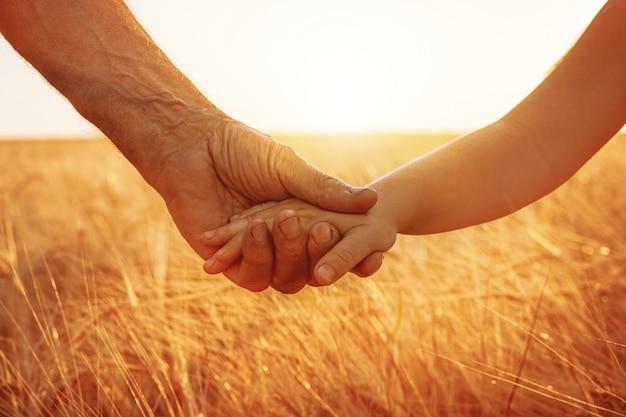 De hand van een klein meisje en de hand van een oudere man.