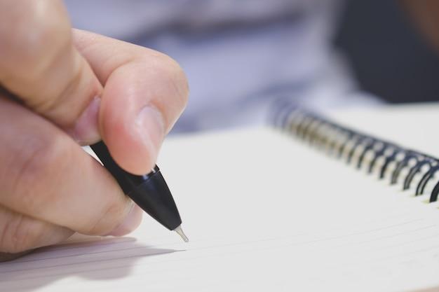 De hand van een man die een boek schrijft met een pen. clouse omhoog.