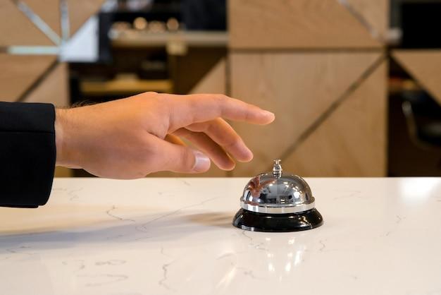 De hand van een man gaat een vintage hotelbel gebruiken