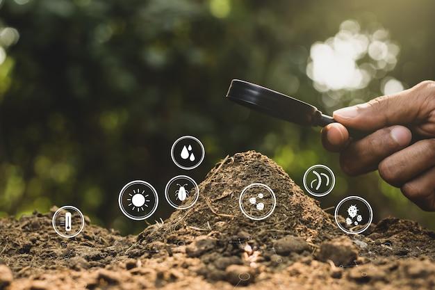 De hand van een man gebruikt een vergrootglas om de mest te laten schijnen met de technologiepictogrammen eromheen