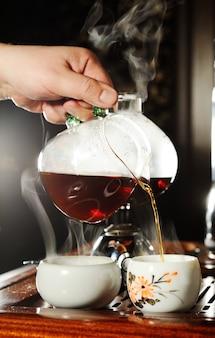 De hand van een man giet zwarte thee in een mooie chinese kom