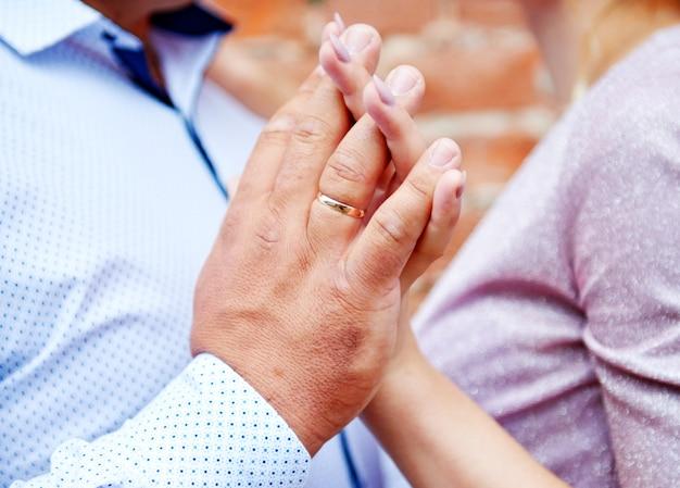 De hand van een man houdt de hand van een vrouw in een kasteelclose-up met trouwringen op een rode bakstenen muur.