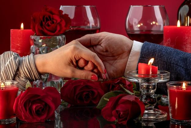 De hand van een man houdt de hand van een vrouw vast met een rode manicure tussen smeltende kaarsen