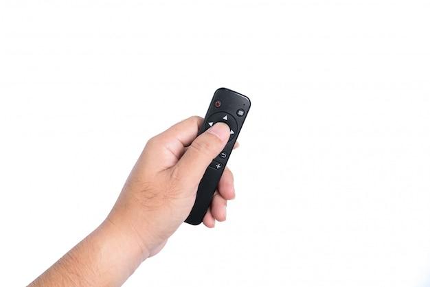 De hand van een man houdt een afstandsbediening van een tv vast.