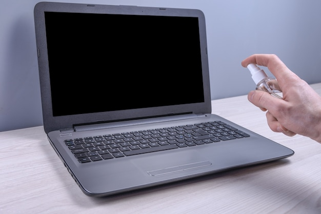 De hand van een man houdt een desinfecterende spray vast en klikt erop en desinfecteert de laptop, de computer om te desinfecteren