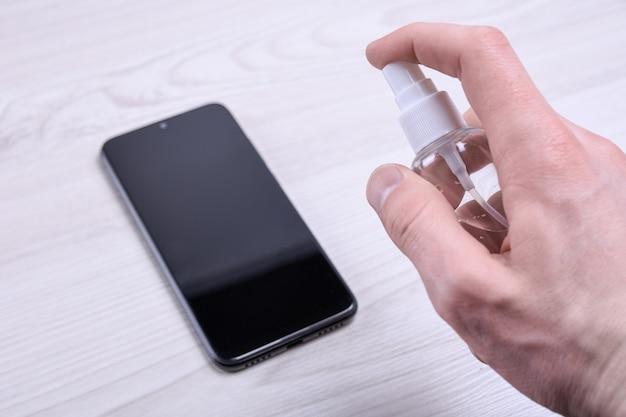 De hand van een man houdt een desinfecterende spray vast en klikt erop en desinfecteert de laptop