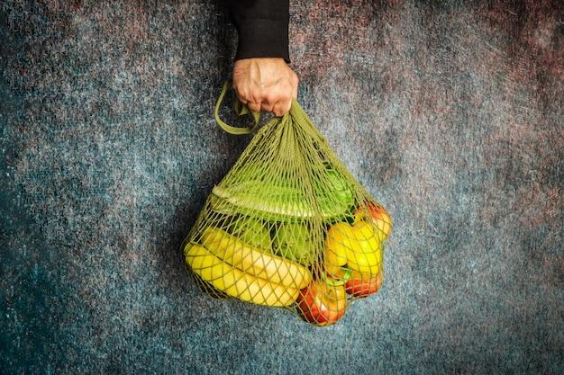De hand van een man houdt een groene koordzak met verse groenten en fruit vast. geen plastic, alleen natuurlijke materialen en natuurlijke producten.