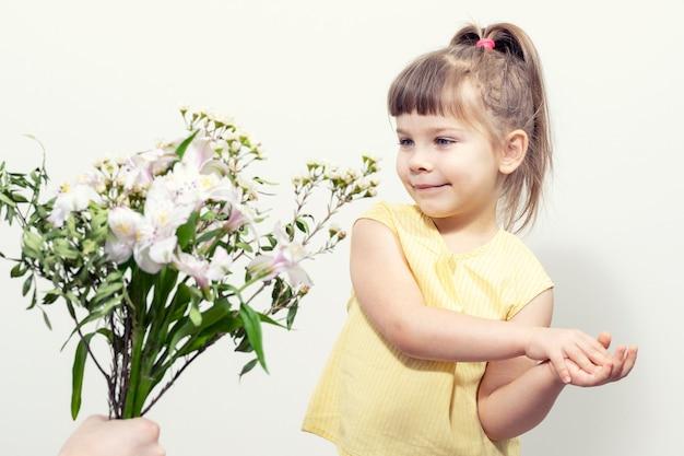 De hand van een man houdt een schattig klein meisje een boeket witte bloemen voor
