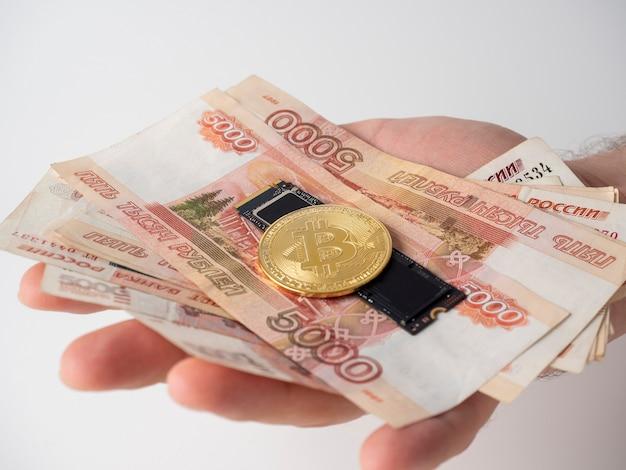 De hand van een man houdt russische bankbiljetten, een m2 ssd-schijf en bitcoin vast. het concept van het verdienen en delven van geld op harde media