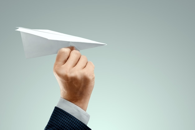 De hand van een man in een pak houdt een papieren vliegtuigje vast. opstartconcept, lichte zaken, aan de slag. kopieer ruimte.