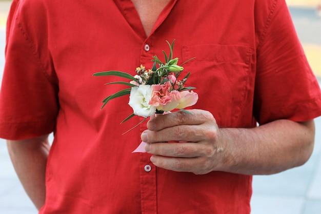 De hand van een man in een rood shirt houdt een klein mooi boeket vast