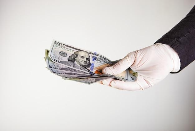 De hand van een man in een witte medische handschoen houdt geld in de vorm van honderd-dollarbiljetten. bescherming tegen virussen en bacteriën. concept. covid-19 of coronavirus
