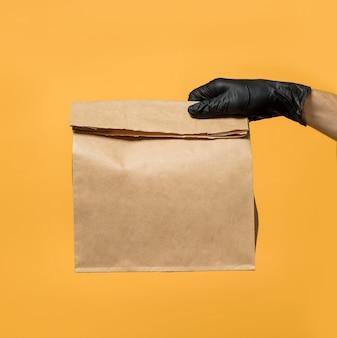 De hand van een man in een zwarte beschermende handschoen houdt een papieren zak vast