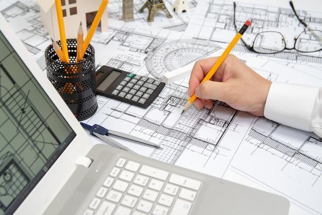 De hand van een mannelijke architect die een ontwerp met een potlood tekent.
