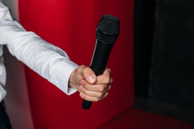 De hand van een mannelijke presentator, verslaggever, journalist houdt een microfoon op een rode muur