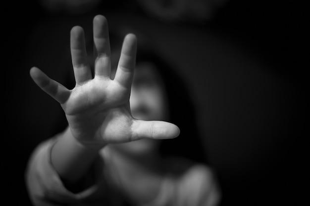 De hand van een meisje in het donker