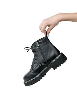 De hand van een meisje met een grote zwarte geïsoleerde schoen. casual stijlvolle schoenen.