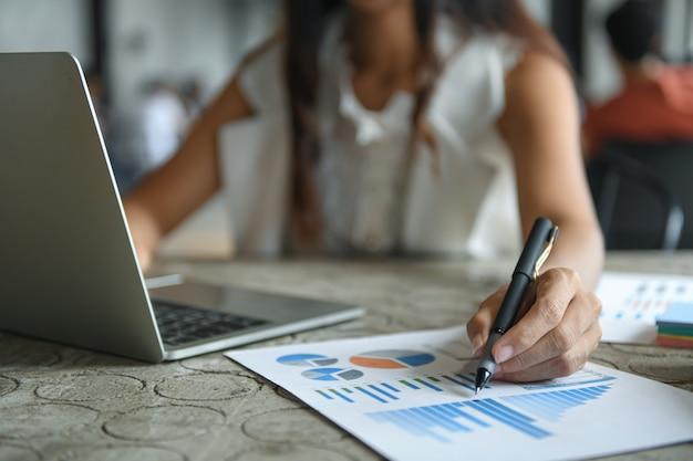 De hand van een onderneemster houdt een pen wijzend op de grafiek en gebruikt laptop.