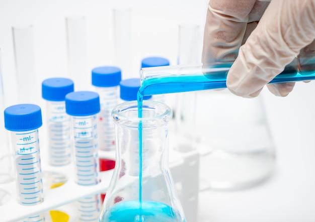 De hand van een onderzoeker die een reageerbuis met blauwe vloeistof houdt.