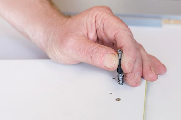 De hand van een oudere man zet de sluiting vast tijdens de montage van meubels