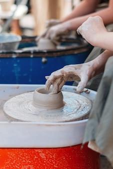 De hand van een persoon creëert een kleifiguur in aardewerk.