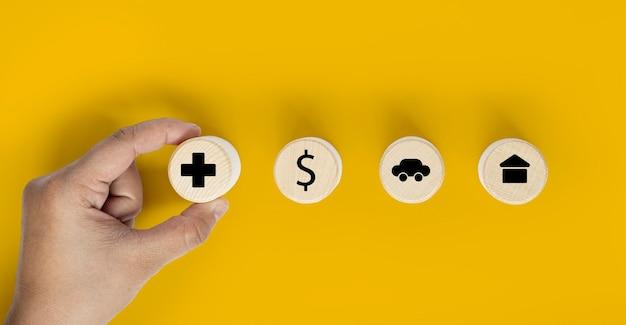 De hand van een persoon houdt een cirkelvormig houten blok vast met een verzekeringspictogram dat tegen een houten blok, een geldpictogram, een auto en een huis is geplaatst. verzekeringsconcept. uitknippad en kopieer ruimte.