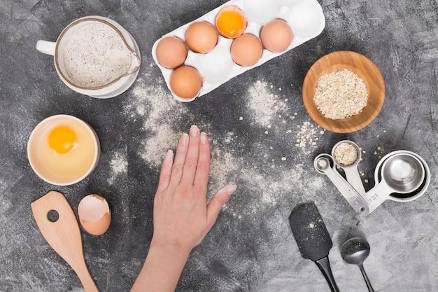 De hand van een persoon met broodingrediënten op zwarte geweven achtergrond