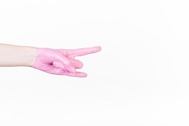 De hand van een persoon met roze verf die hoornteken maakt