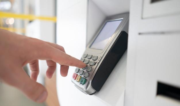 De hand van een persoon voert het wachtwoord in en drukt op knoppen om een betaling uit te voeren Premium Foto