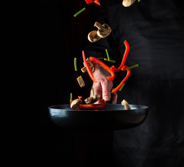 De hand van een professionele chef-kok gooit stukjes groenten en champignons op een koekenpan op een zwarte achtergrond. restaurant kookconcept. gratis advertentieruimte