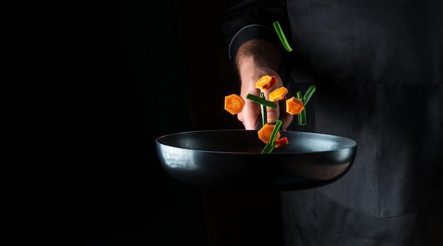 De hand van een professionele chef-kok gooit stukjes groenten op een koekenpan op een zwarte achtergrond. restaurant kookconcept. gratis advertentieruimte