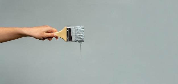 De hand van een reparateur met een penseel kleurt de muur blauw.
