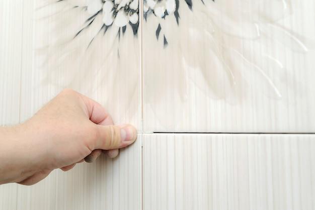 De hand van een tegelzetter legt een afstandhouder voor tegels