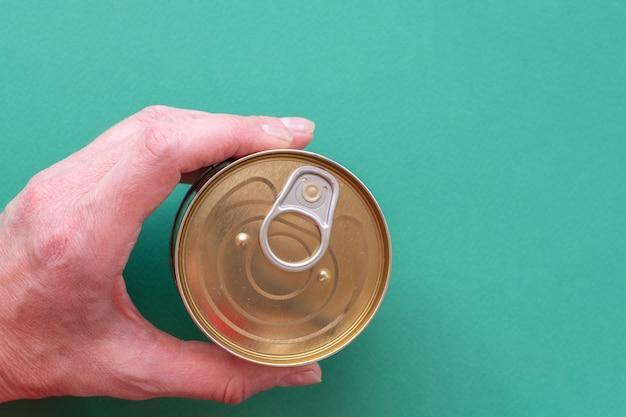 De hand van een volwassen man houdt een gesloten blikje ingeblikt voedsel vast met een openbare sleutel op een groene achtergrond. bovenaanzicht van blikje met ring pull geïsoleerd op groene achtergrond met kopie ruimte. detailopname