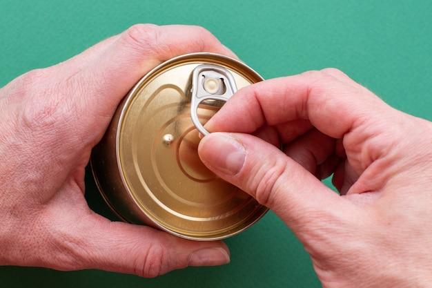 De hand van een volwassene houdt een blikje ingeblikt voedsel vast, de tweede hand trekt aan de sleutel, opent het blik. bovenaanzicht op groene achtergrond met kopie ruimte. detailopname