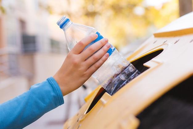 De hand van een vrouw die een plastic fles recyclet