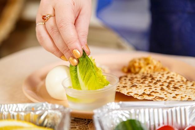 De hand van een vrouw doopt een blad sla in zout water tijdens de pesach seder. horizontale foto