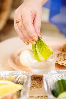De hand van een vrouw doopt een blad sla in zout water tijdens de pesach seder. verticale foto