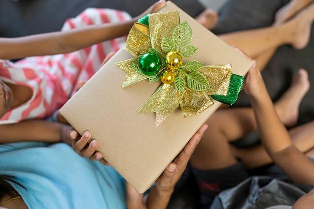 De hand van een vrouw, een meisje en een jongen met een bruine kerstcadeau doos