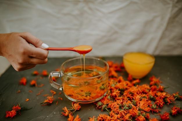 De hand van een vrouw giet honing van een lepel in een kopje bloementhee in een grote doorzichtige mok.