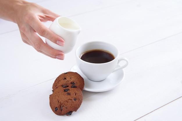 De hand van een vrouw giet melk in koffie. een kop geurige koffie en koekjes