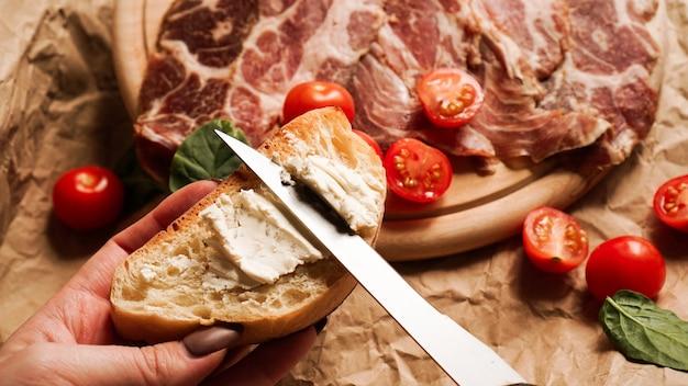 De hand van een vrouw houdt een bruschetta en verspreidt kwark met een mes